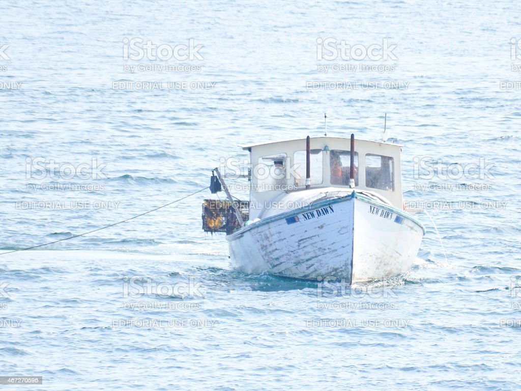 Lobsterboat preparing to haul traps stock photo