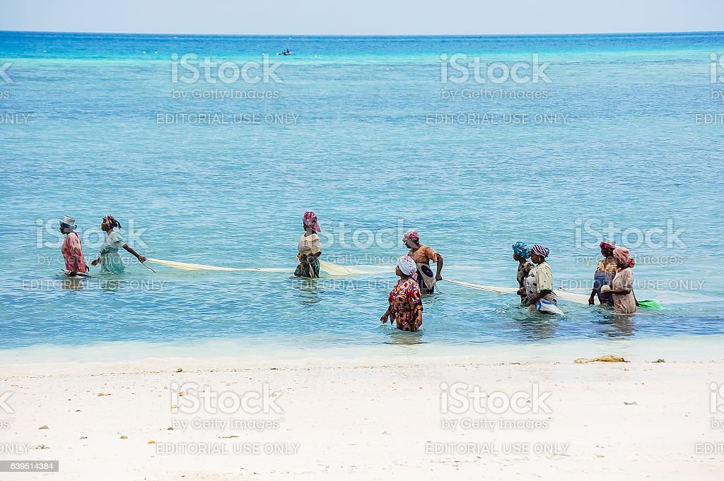 Local African women fishing at tropical beach stock photo