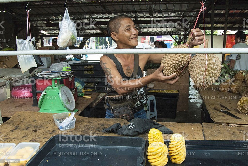 Local Chinese Malaysian Market Trader selling Durian royalty-free stock photo