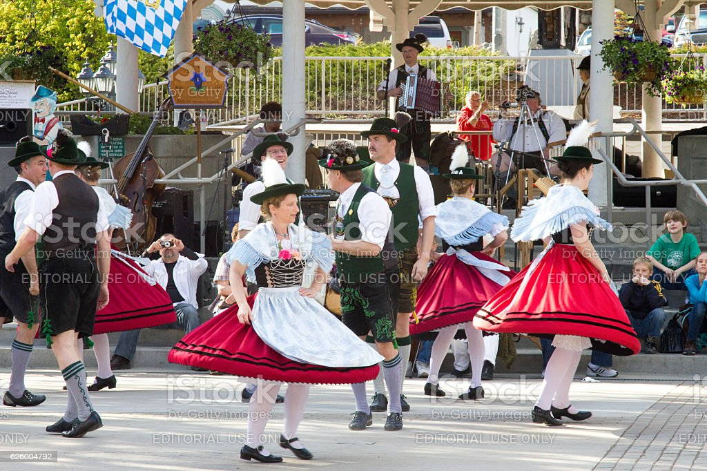 Local citizens performing dance wearing traditional bavarian attire stock photo