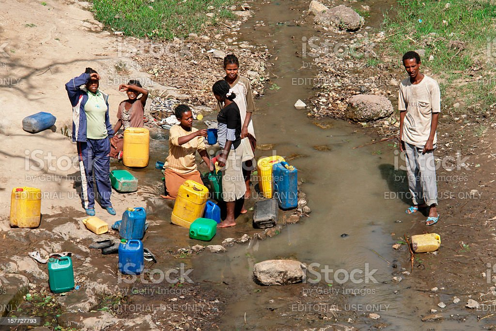Local ethiopians taking water to plastic canisters stock photo