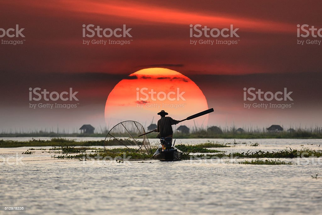 Local fisherman in sunset background stock photo