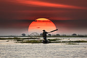 Local fisherman in sunset background