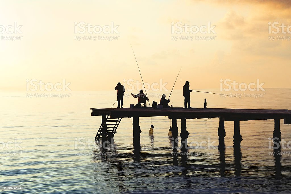 Local fishermen catch fish from the pier. stock photo