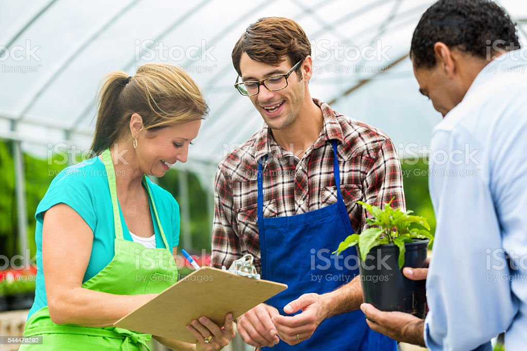 Local garderners and constumer in a greenhouse stock photo