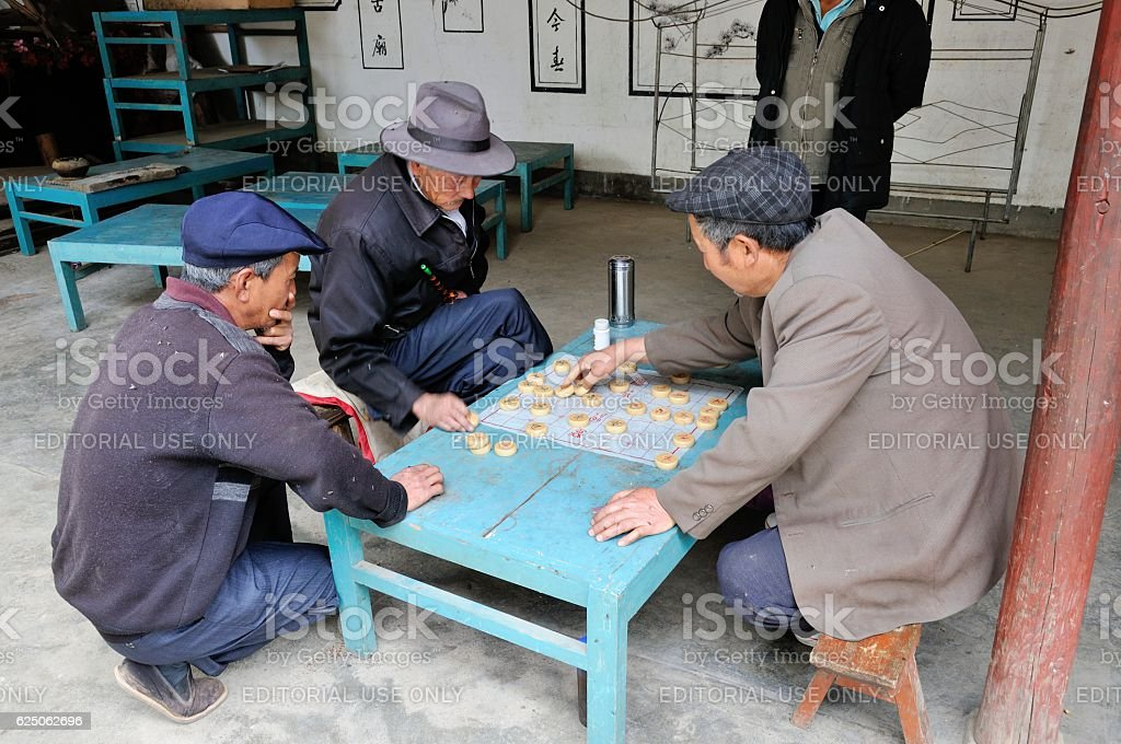 Local people enjoy playing Chinese Chess at temple in Shaxi stock photo