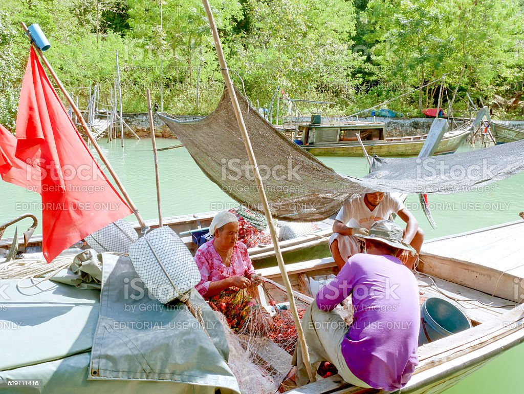 Local people untangle fishing nets on a boat stock photo