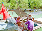 Local people untangle fishing nets on a boat