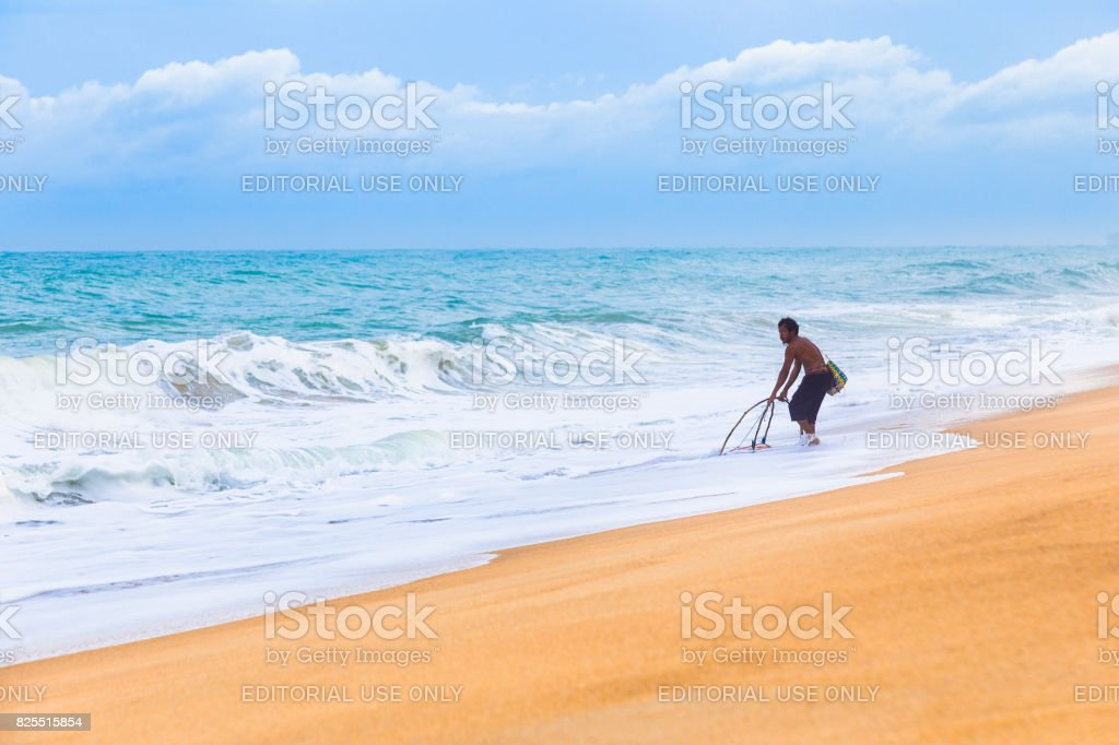 local Phuket fisherman tries to catch fish with his primitive tool at a Phuket beach stock photo