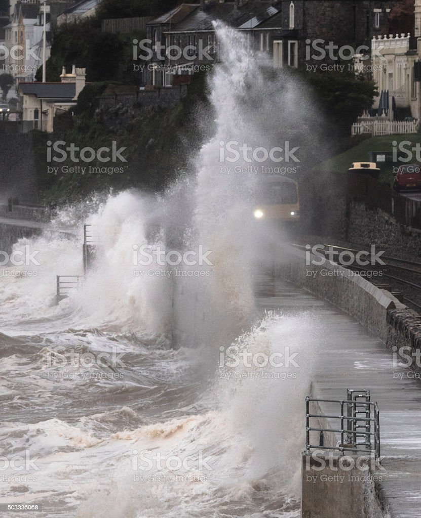 Local train drenched at Dawlish alongside the repaired sea wall stock photo