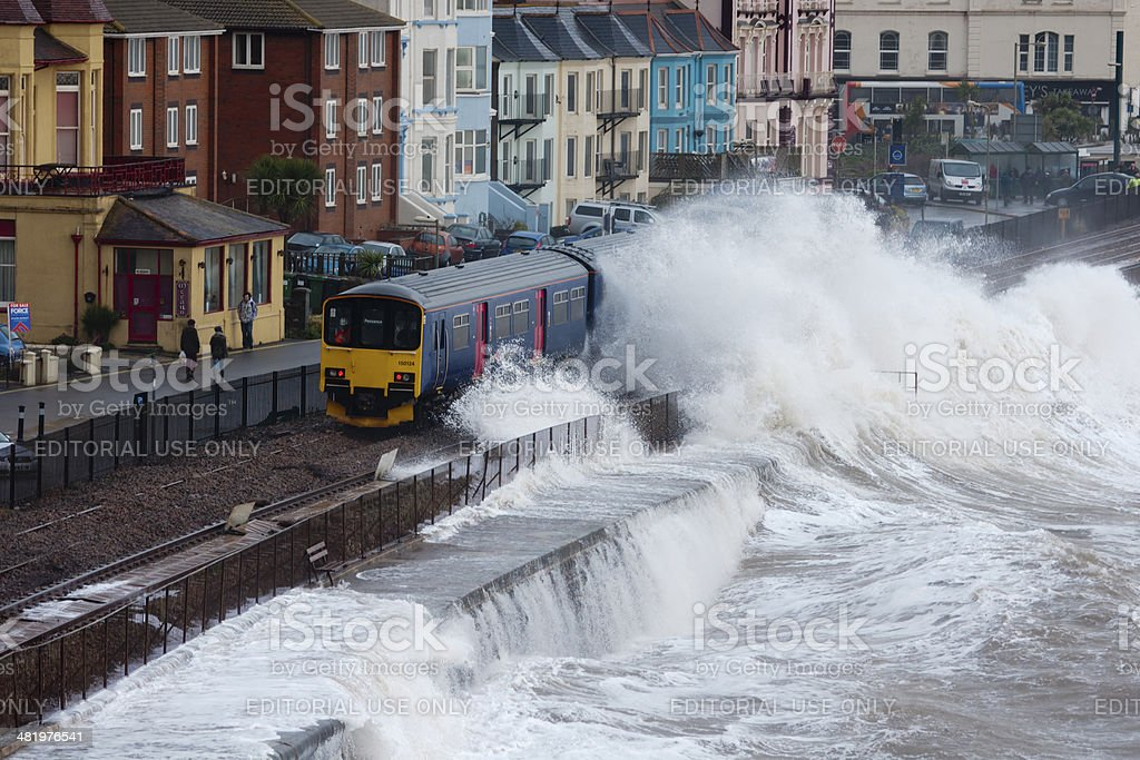 Local train passing Dawlish station during severe storm stock photo