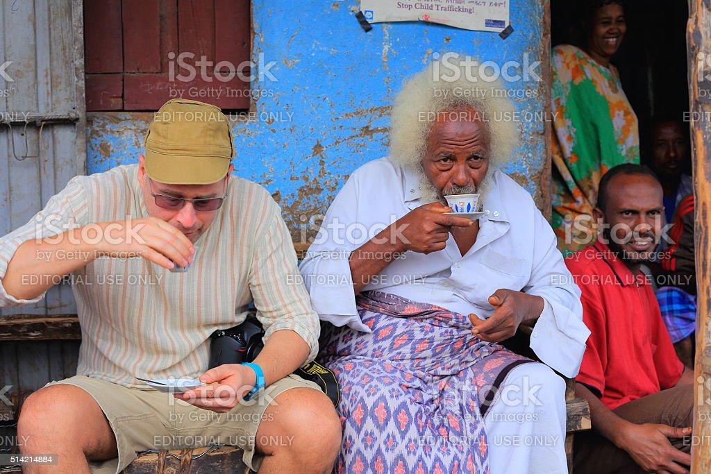 Local VIP and tourist share a coffe cup. Degan-Ethiopia. 0107 stock photo