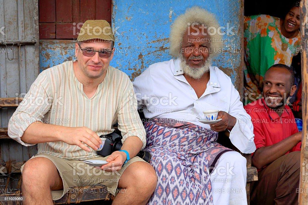 Local VIP and tourist share a coffe. Degan town-Ethiopia. 0106 stock photo