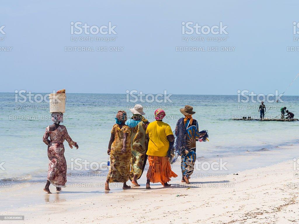 Local women going fishing on a beach in Zanzibar, Tanzania. stock photo