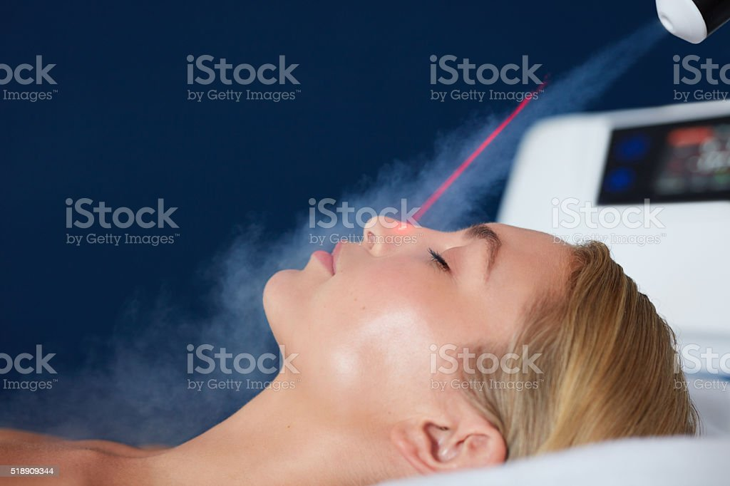 Localized cryotherapy on woman face stock photo