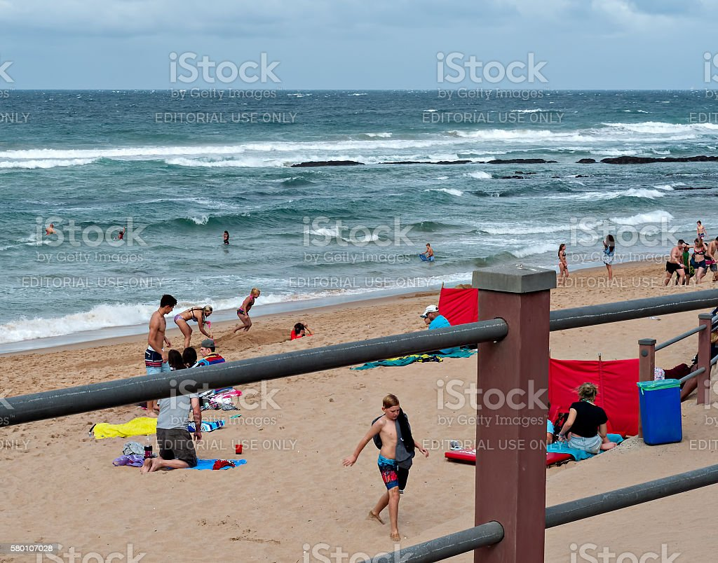 Locals and tourists on the beach stock photo