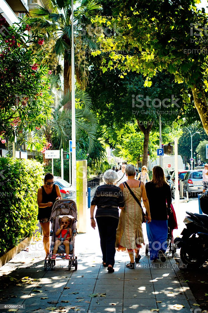 Locals walking along a tree lined avenue in Nice, France stock photo