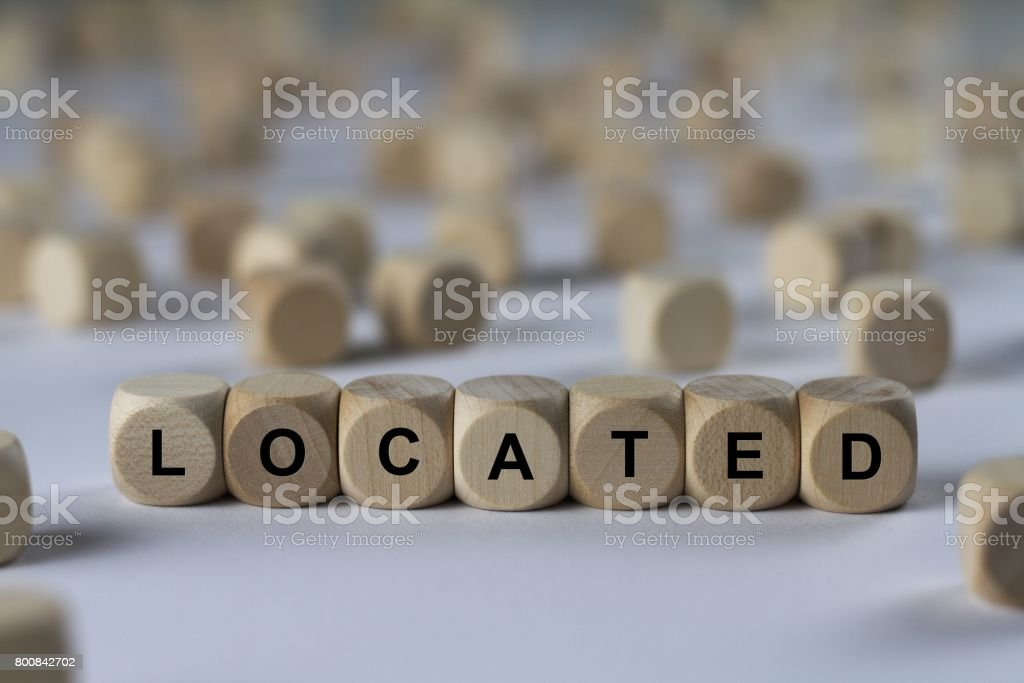 located - cube with letters, sign with wooden cubes stock photo
