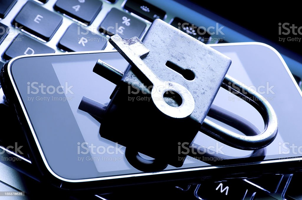 A lock and key on top of a smartphone to show security royalty-free stock photo