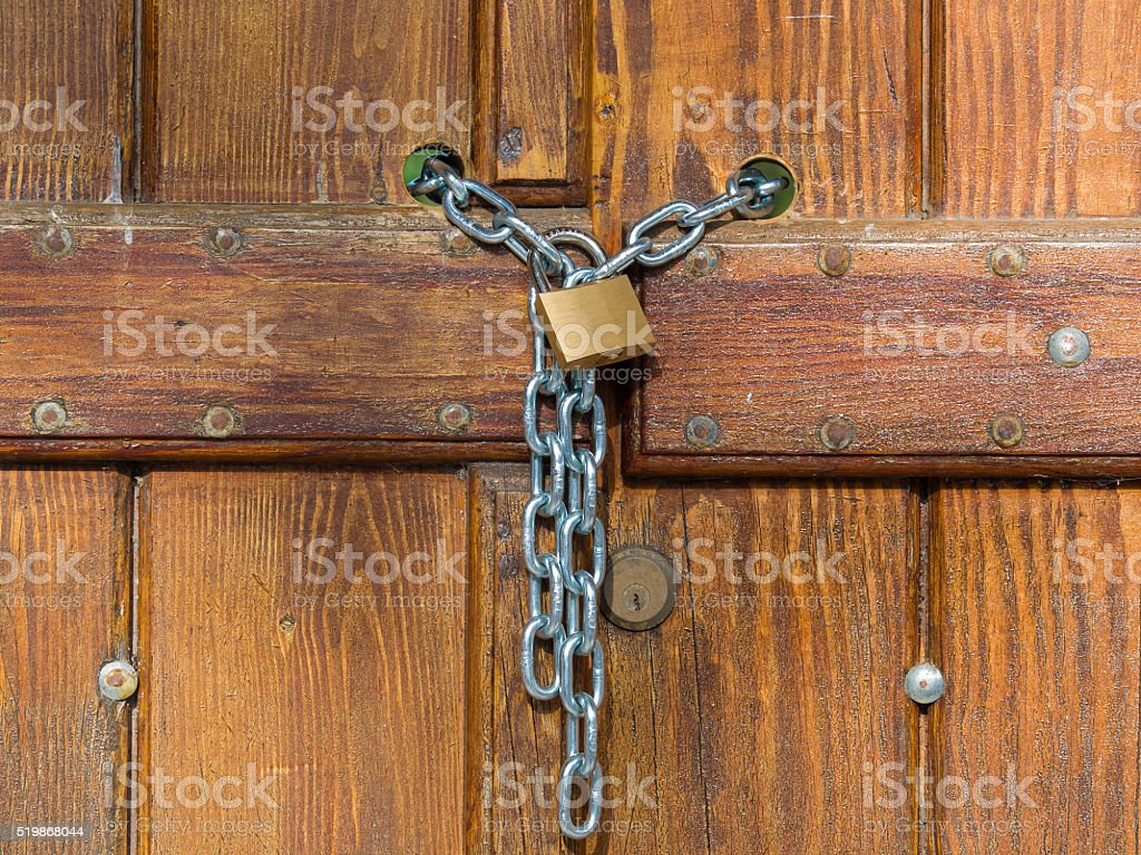 Lock  and shiny chain closing a wooden gate stock photo