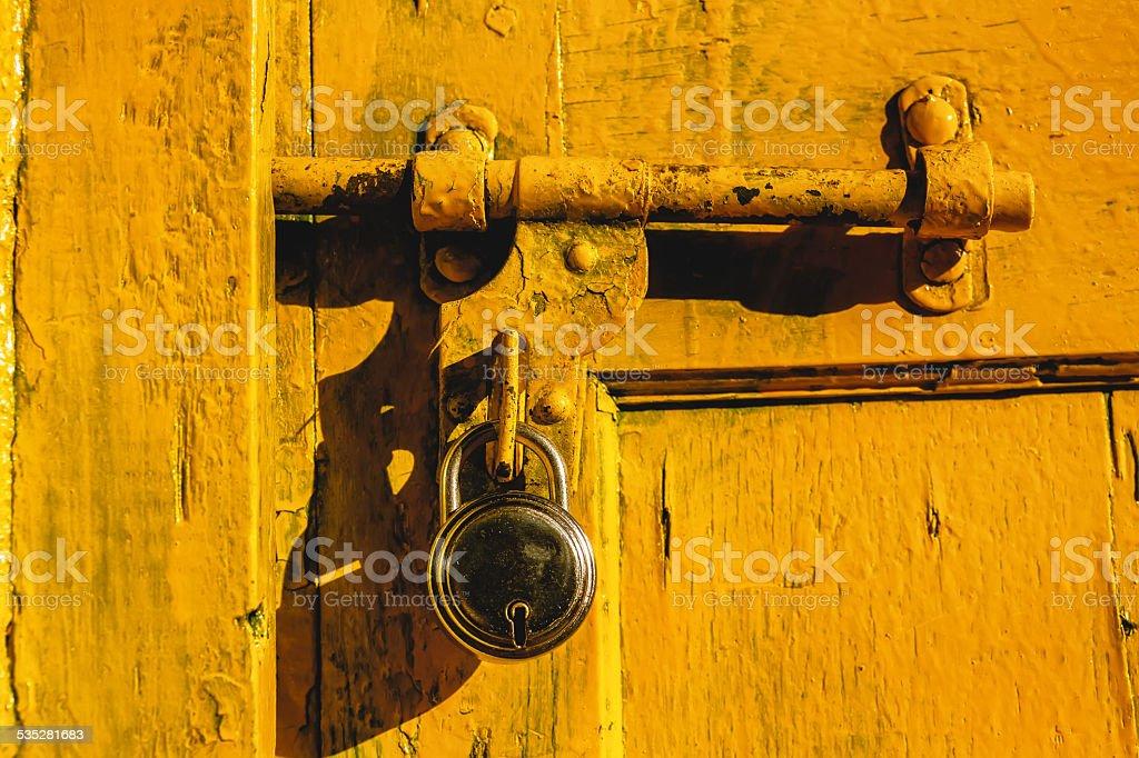 Lock on a rusty yellow door stock photo