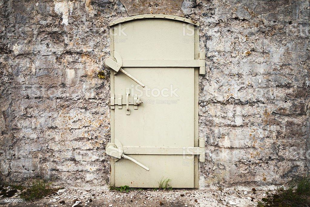 Locked massive metal door in old wall stock photo