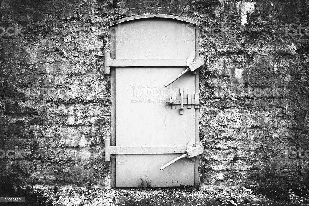 Locked metal door in old fortification wall stock photo