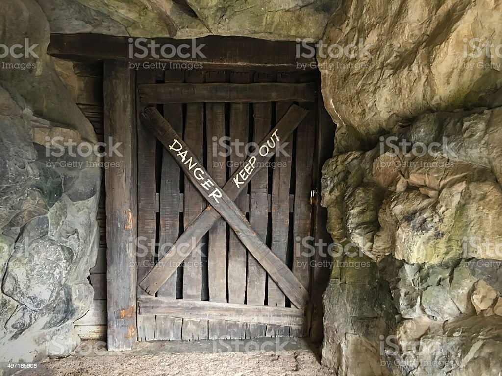 Locked sturdy wooden door with 'keep out' sign stock photo