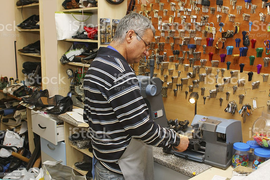 Locksmith at work....making spare key stock photo