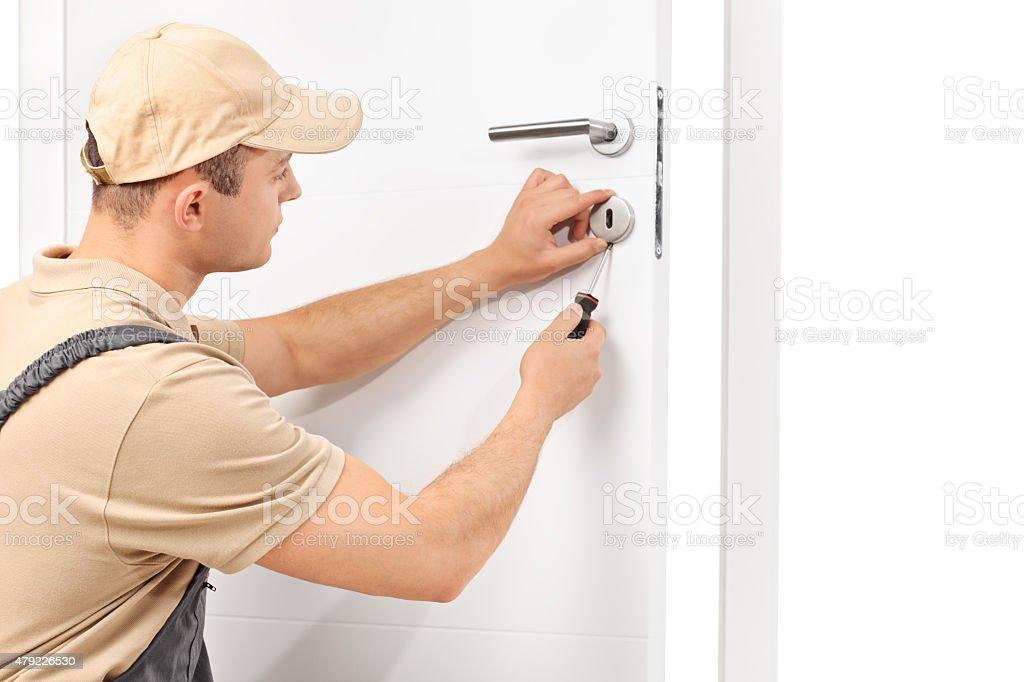 Locksmith installing a lock on a door stock photo