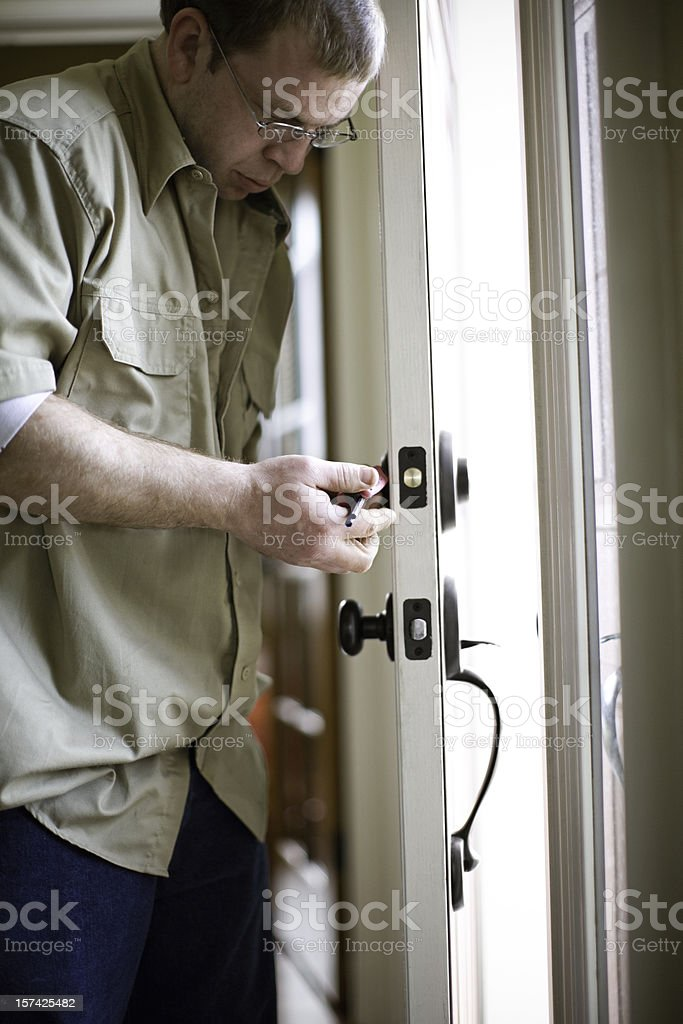 Locksmith Man Changing Door Locks stock photo