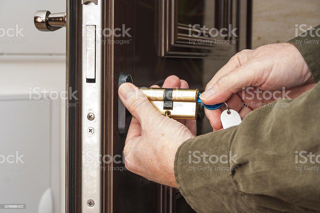 Locksmith replacing a cylinder lock stock photo