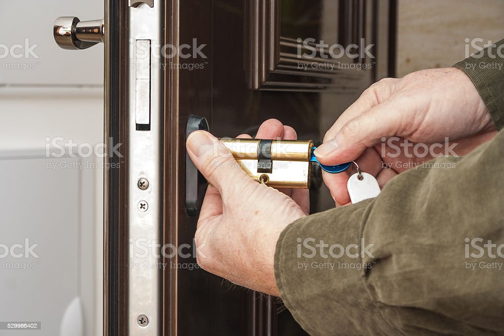 Locksmith replacing a cylinder lock stock photo
