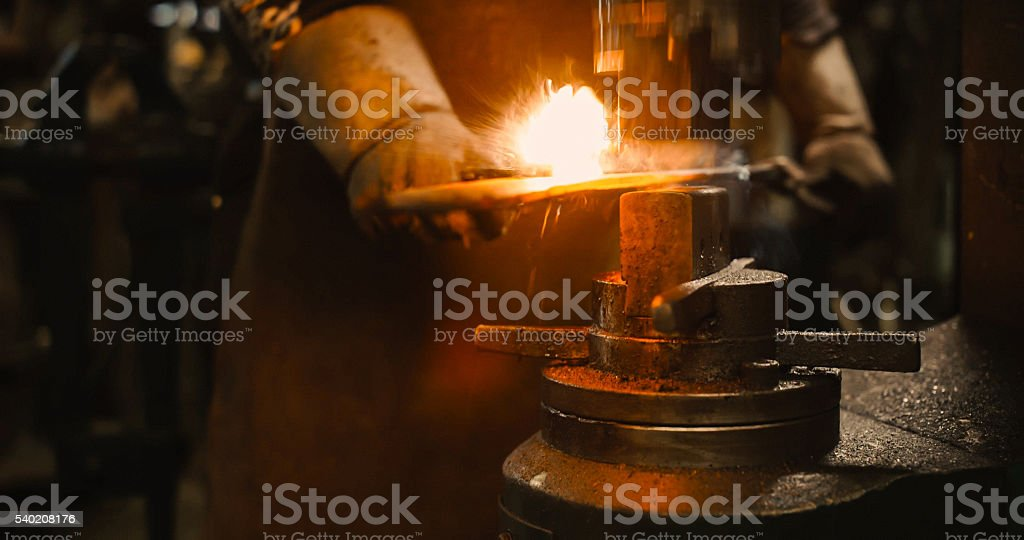 Locksmith working hot iron. stock photo