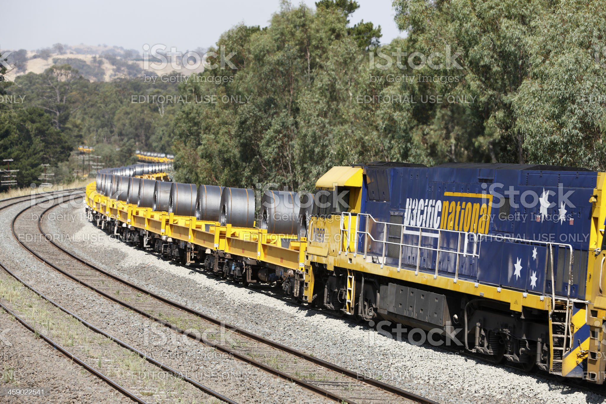 Locomotive with trainload of coiled steel in hills royalty-free stock photo