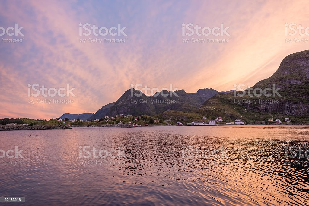 Lofoten, Norway. Fishing village with sharp mountain peaks at su stock photo