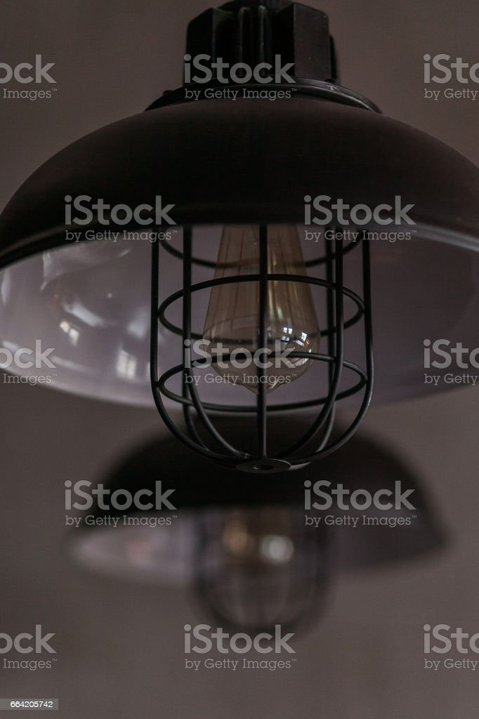 Loft industrial wire pendant lamps against rough wall stock photo
