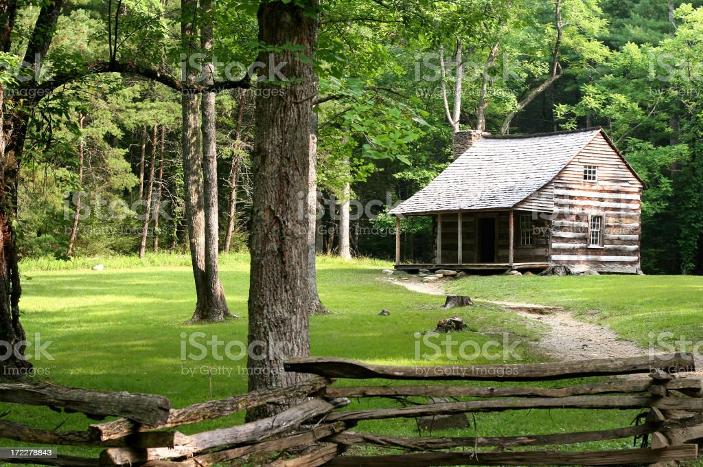 Log cabin in grassed clearing with forest path and fence royalty-free stock photo