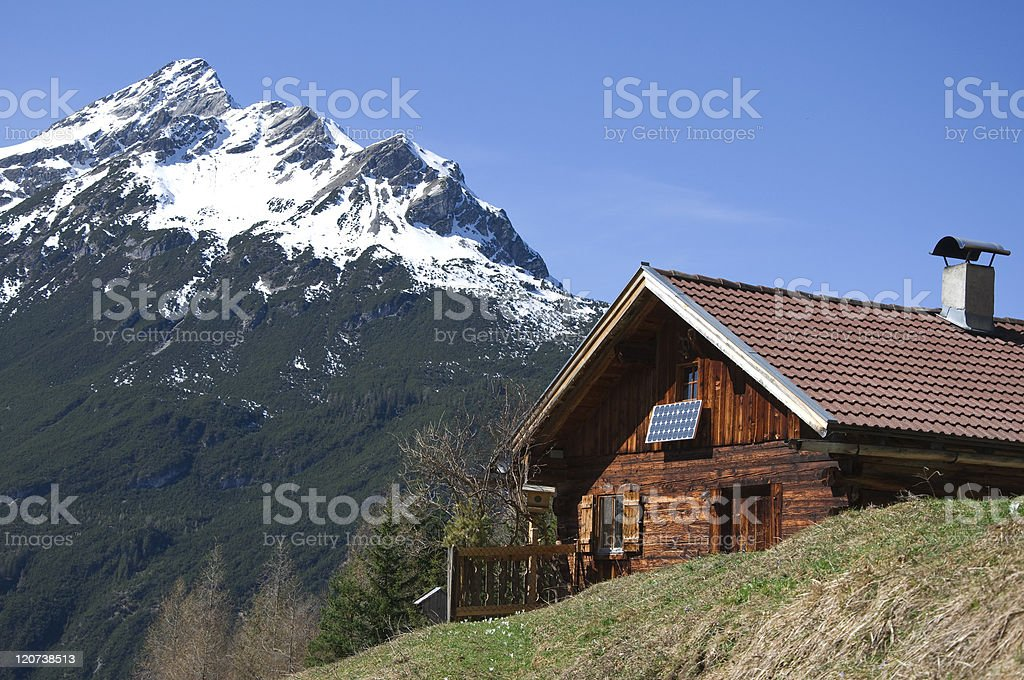 Log cabin in the spring with mountains in the background stock photo
