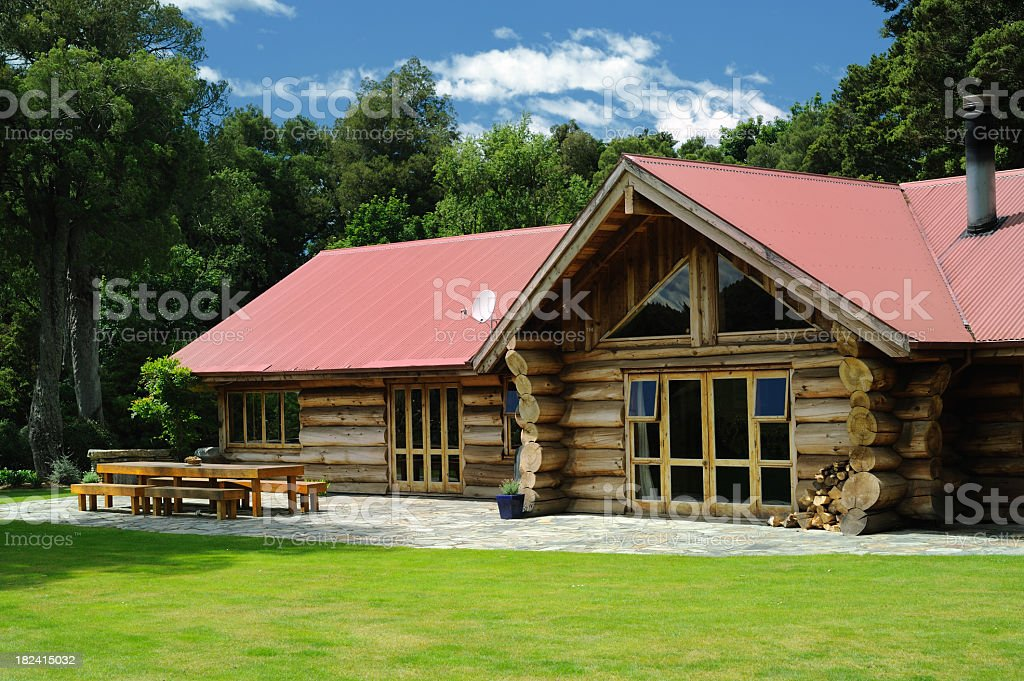 A log cabin near a forest on a sunny day royalty-free stock photo