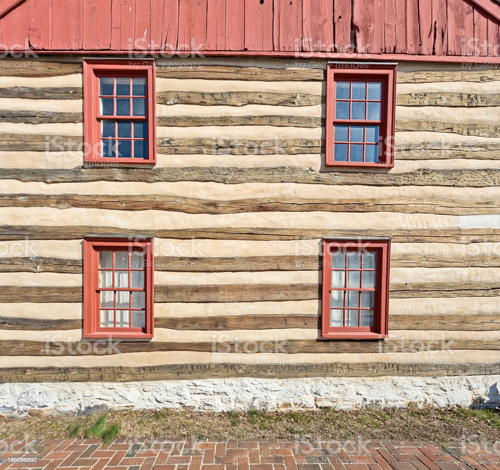 Log Cabin with Red Window Frames and Brick Sidewalk stock photo