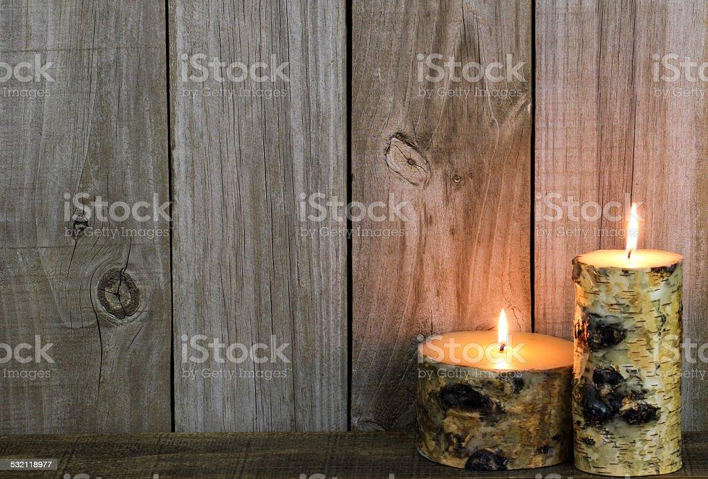 Log candles burning by wood background stock photo
