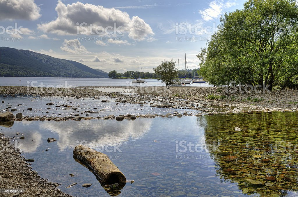 Log on the shore of Coniston Water stock photo