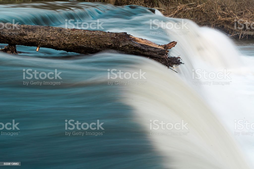 Log on top of waterfall resisting flow of river stock photo