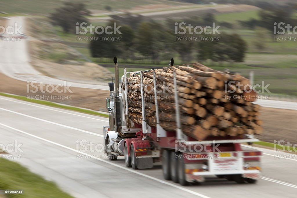 Logging truck going down highway stock photo
