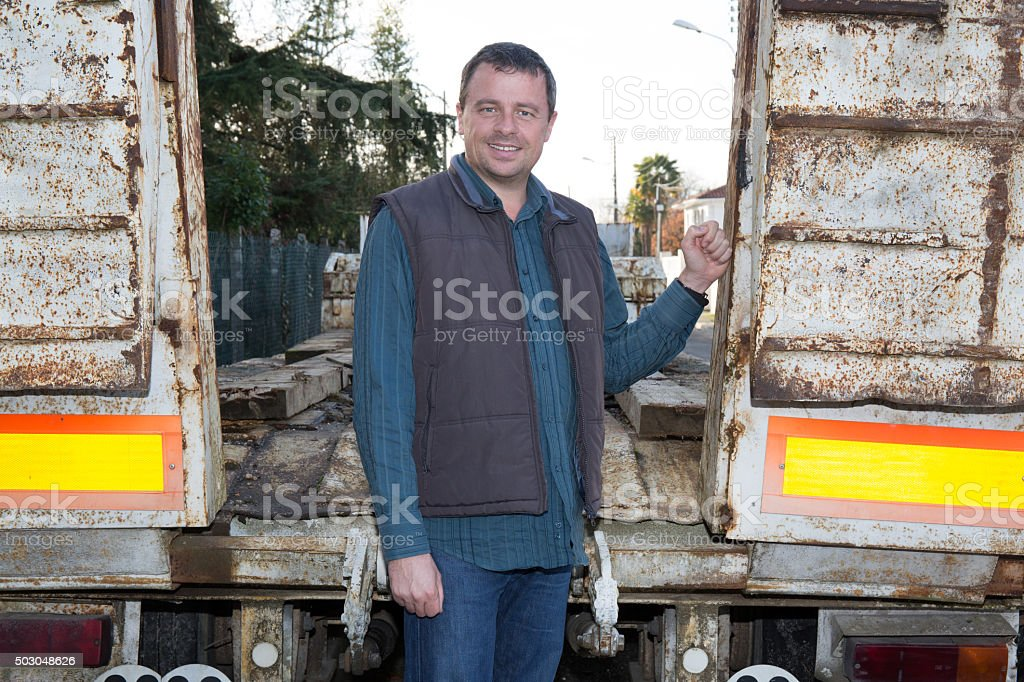 Logistics - confident driver  in front of trucks and trailers stock photo