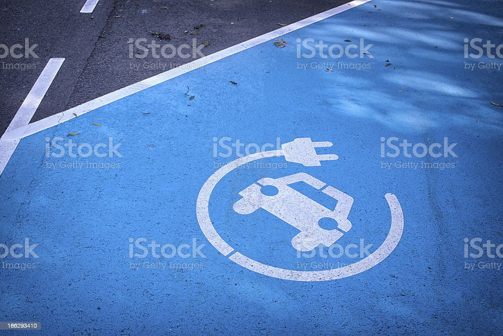 Logo 'charge your car here' on blue parking lot stock photo