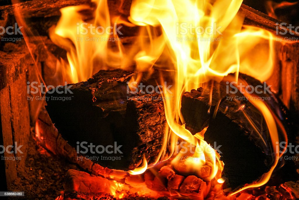 Logs burning hot in fire place. stock photo