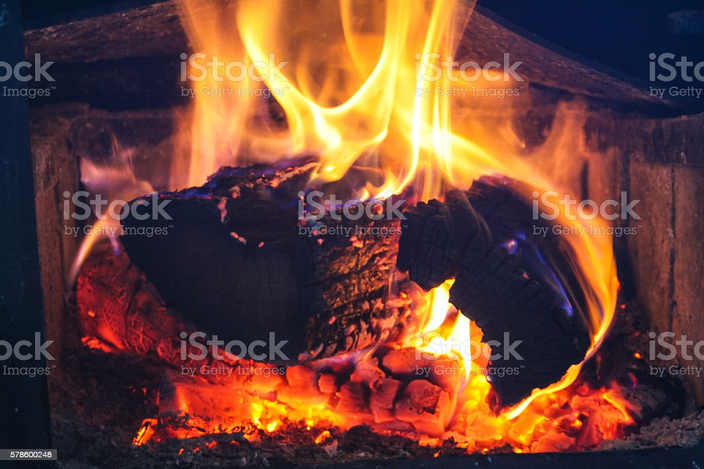 Logs on fire with blue flames and hot ambers. stock photo