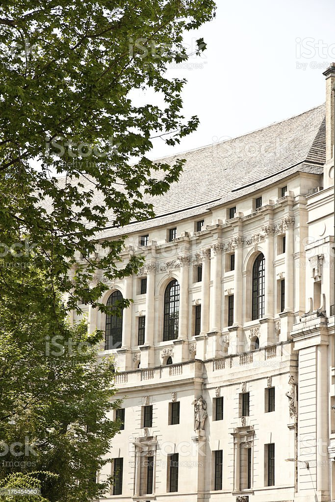 london architecture: classic building facade behind lush tree royalty-free stock photo